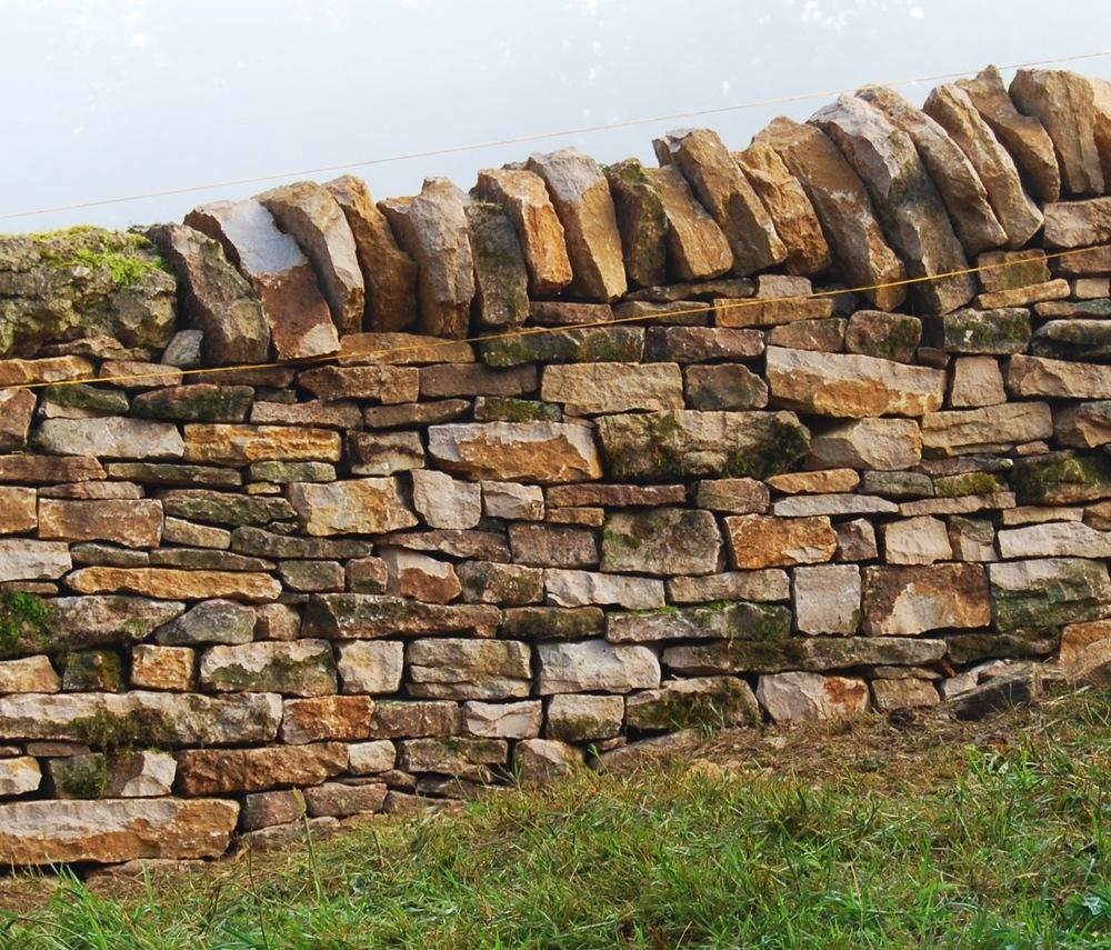 Bruchstein-Schichtenmauerwerk einer ca. 1.2 Meter hohen freistehenden Weide- und Grenzmauer im Jura.