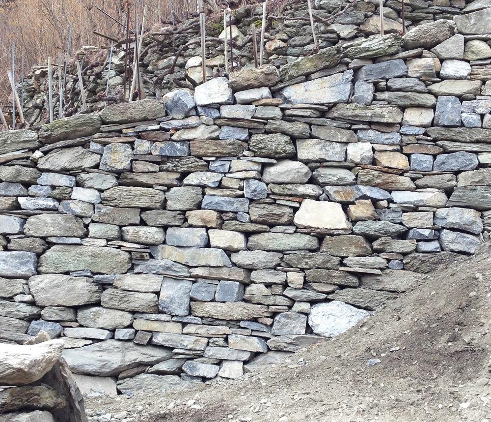 Bruch- und Lesesteinmauerwerk einer ca. 2 Meter hohen Stützmauer in einem Walliser Rebberg.