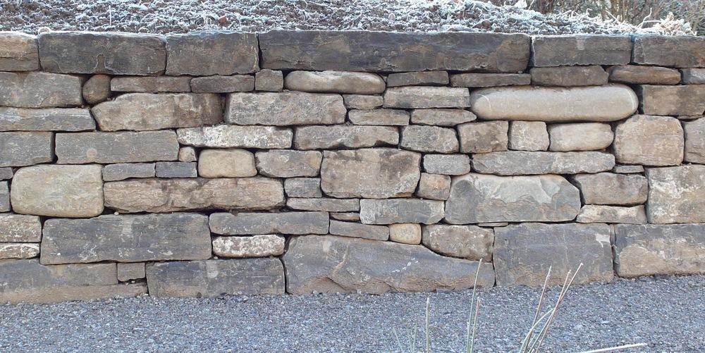Bruchsteinmauerwerk einer ca. 0.9 Meter hohen Gartenstützmauer in einem Privatgarten.