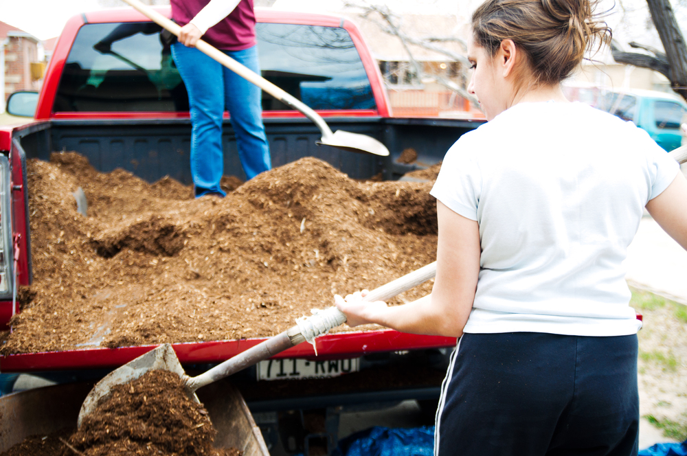 Promotoras delivering compost to a family garden.