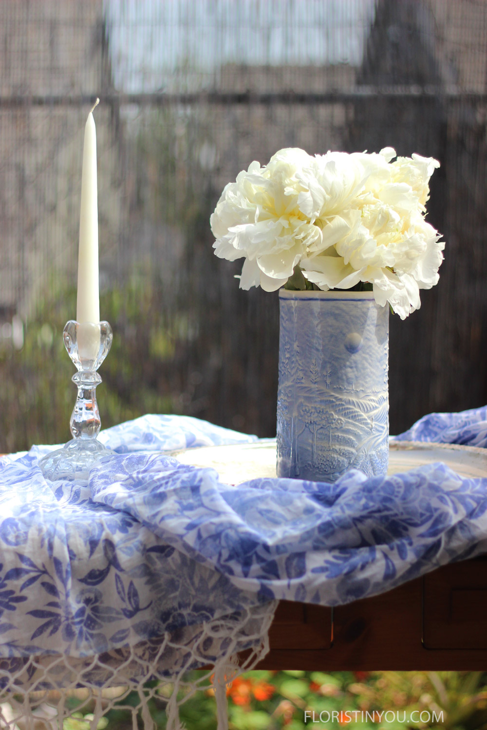Add a beautiful scarf that compliments the arrangement and a candle and candle stick holder.