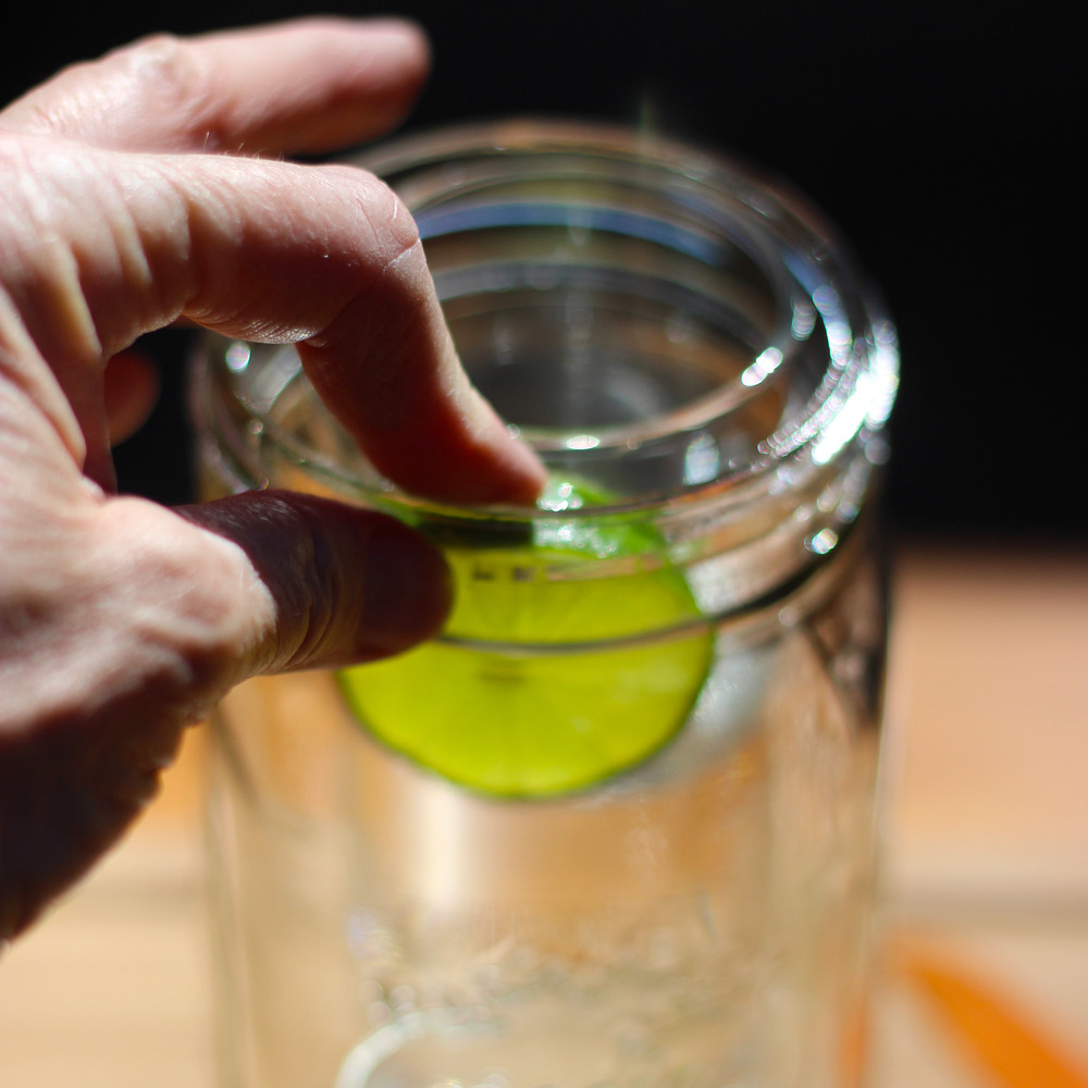 "Push lime slices between cylinder and ""Mason jar"".  Use  table knife to help position."