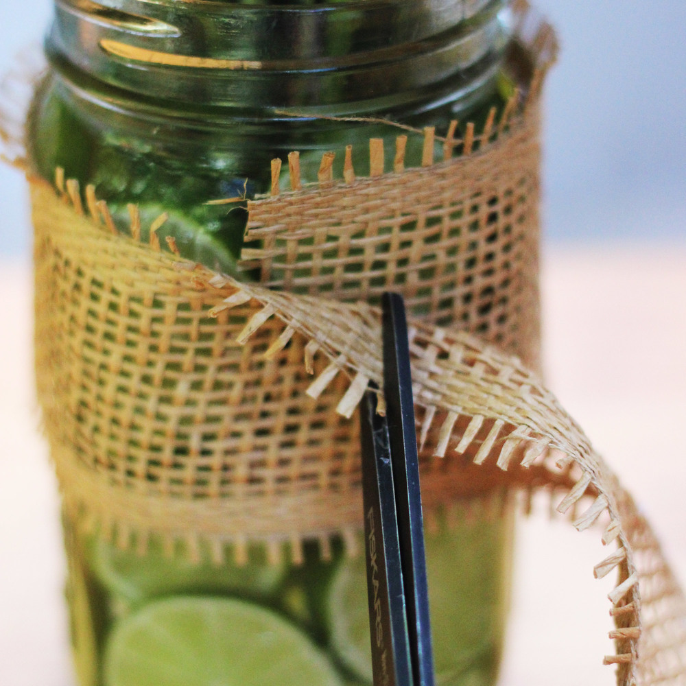 "Hold ribbon tight around ""Mason jar"".  Leave extra inch.  Cut."