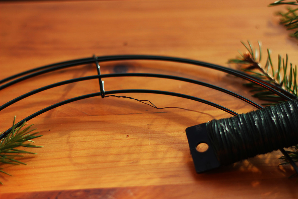 Secure the wire around the top. Wrap it around several times. Use one continuous wire to wrap all the green on with.