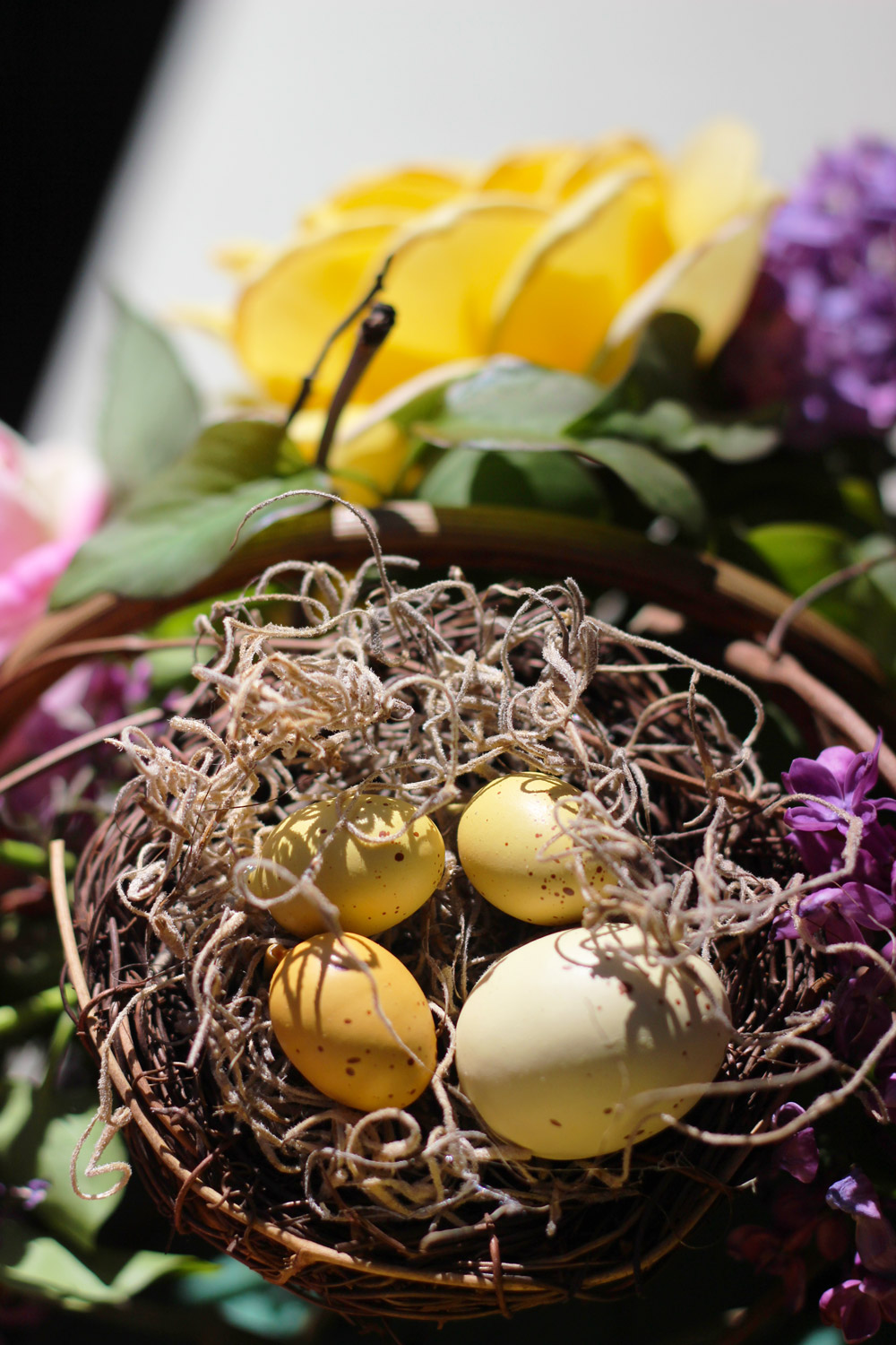 Bend wire on eggs straight down. Put daub hot glue on each egg and position in nest. Push flower pick into foam to position.