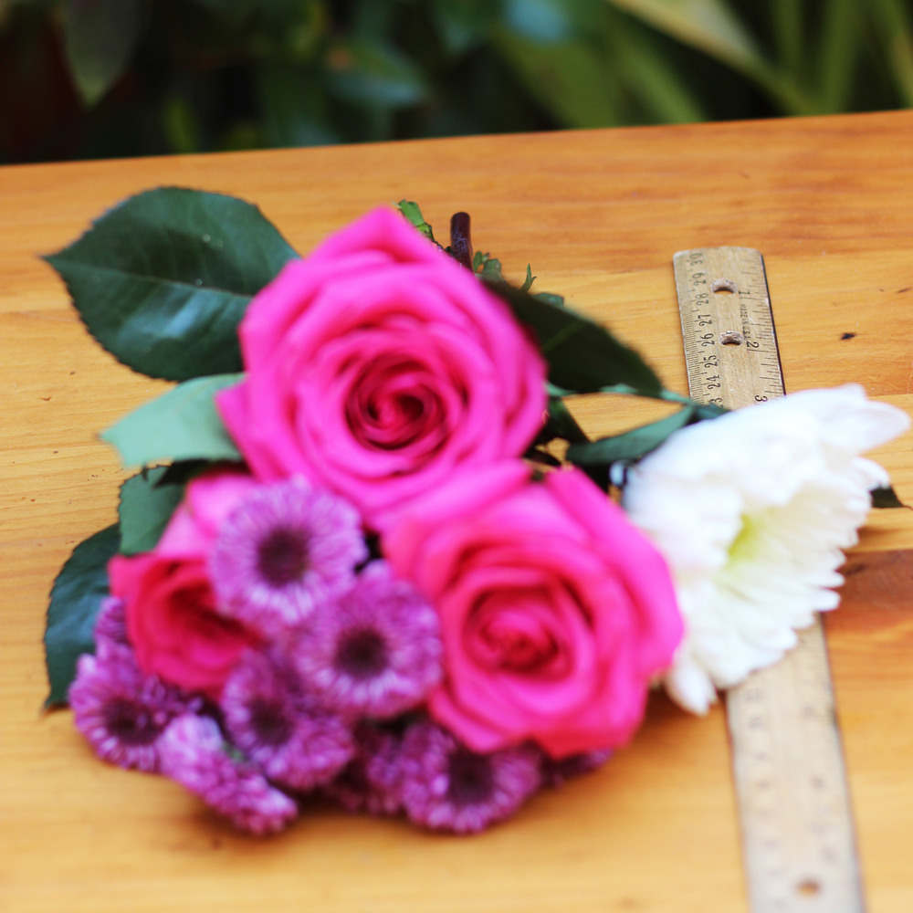 Hold flowers to side of vase to measure.  Cut.  Lowest rose was about 1.25 inches above rim.