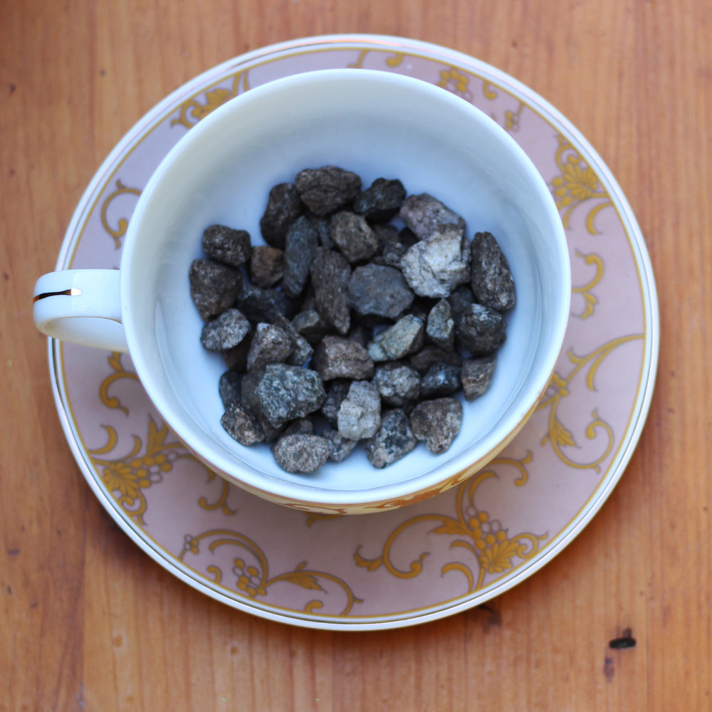 Put a handful of gravel in the cup or drill a 1/2 hole in the bottom of it with a diamond bit.
