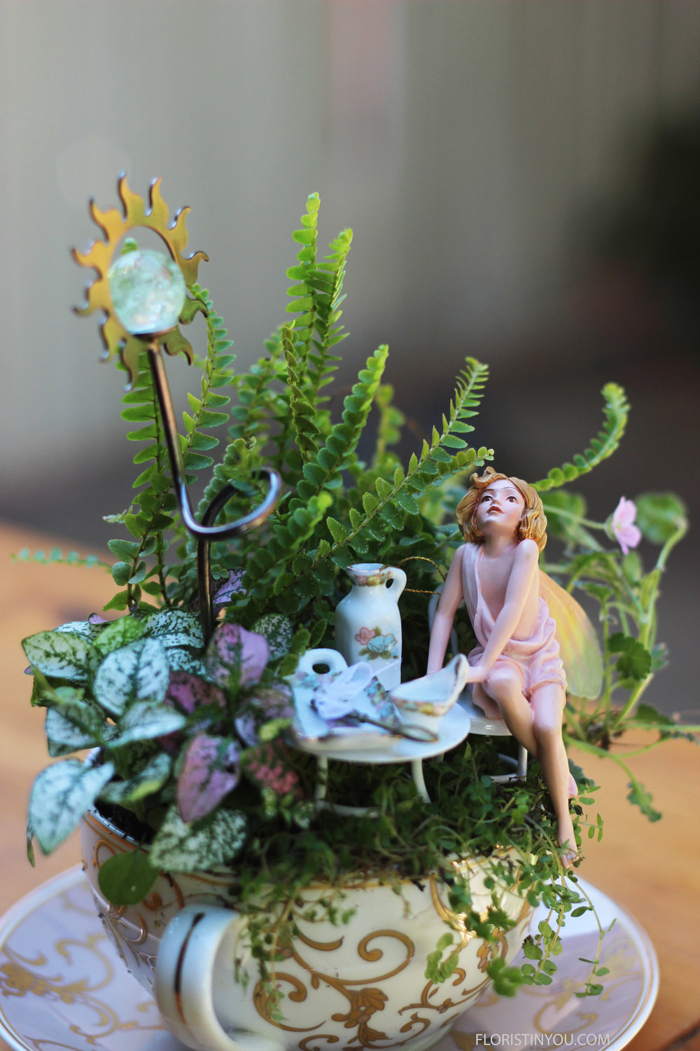 Place clay under fairy and push onto the seat of the chair so she won't fall.  The fairies are delicate and can break.