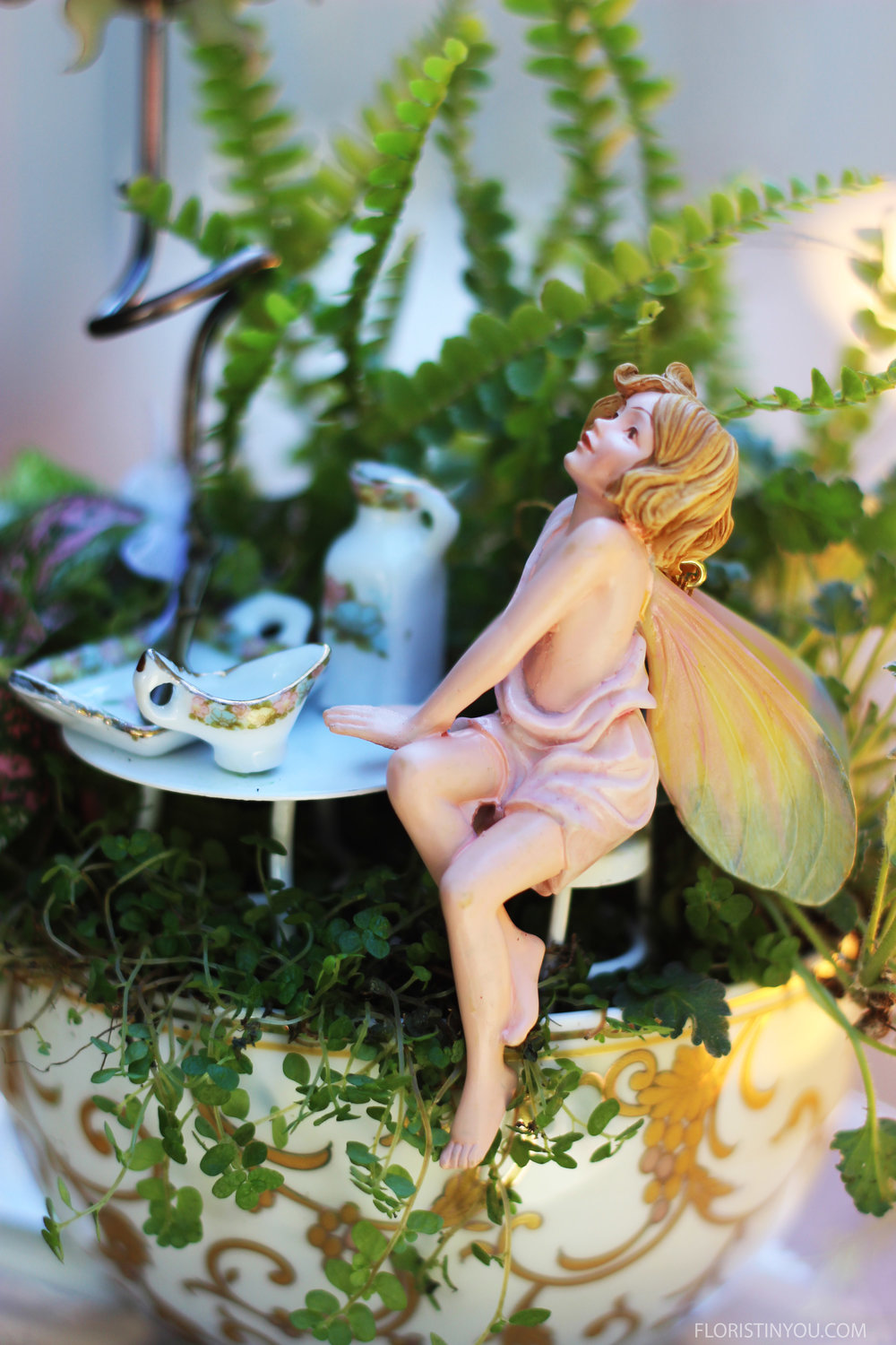 A ray of light catches the curls in her strawberry blond hair, illuminates her wings and shimmers across the gold leaf on the cup.
