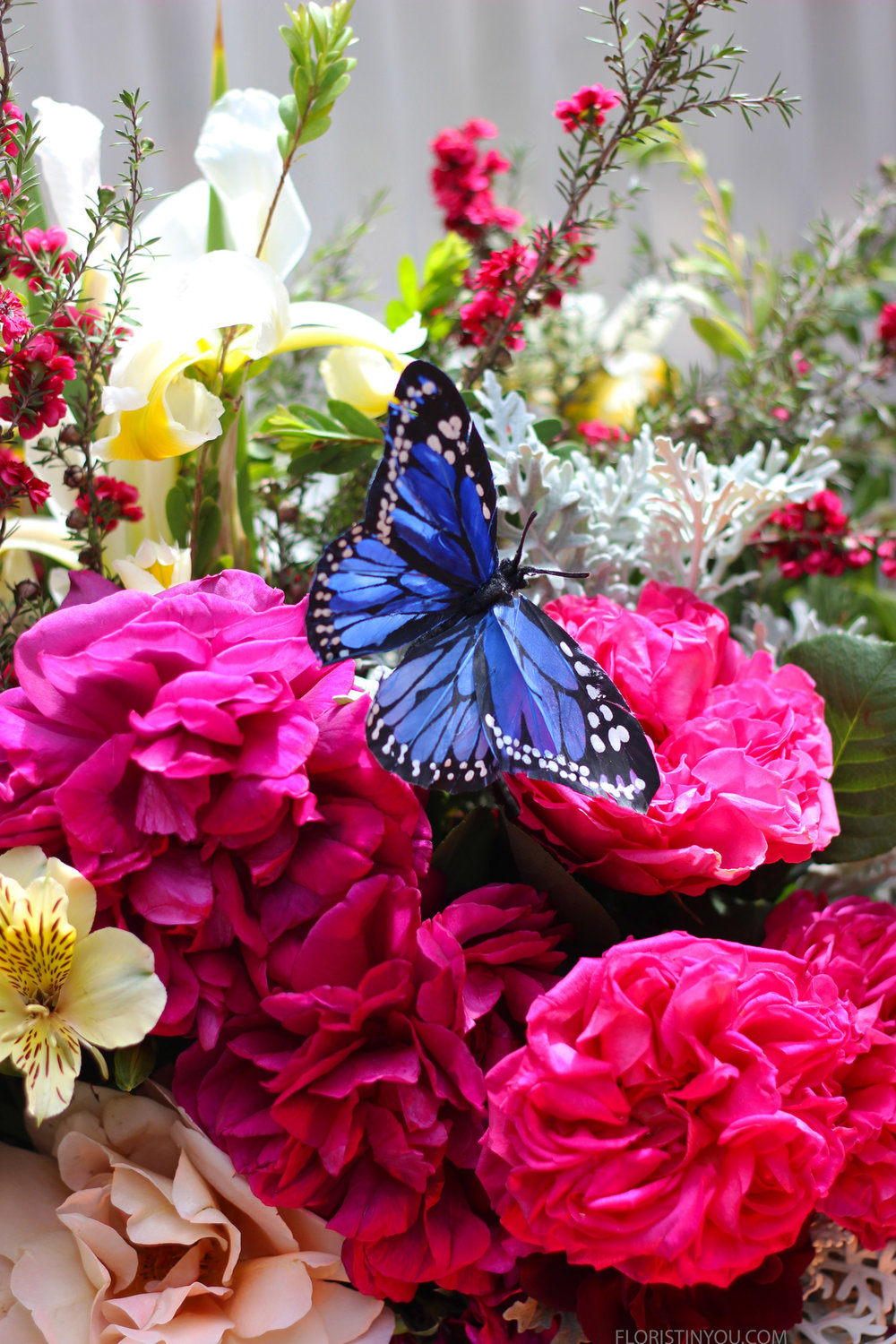 Set butterfly in flowers with wire and pick behind.