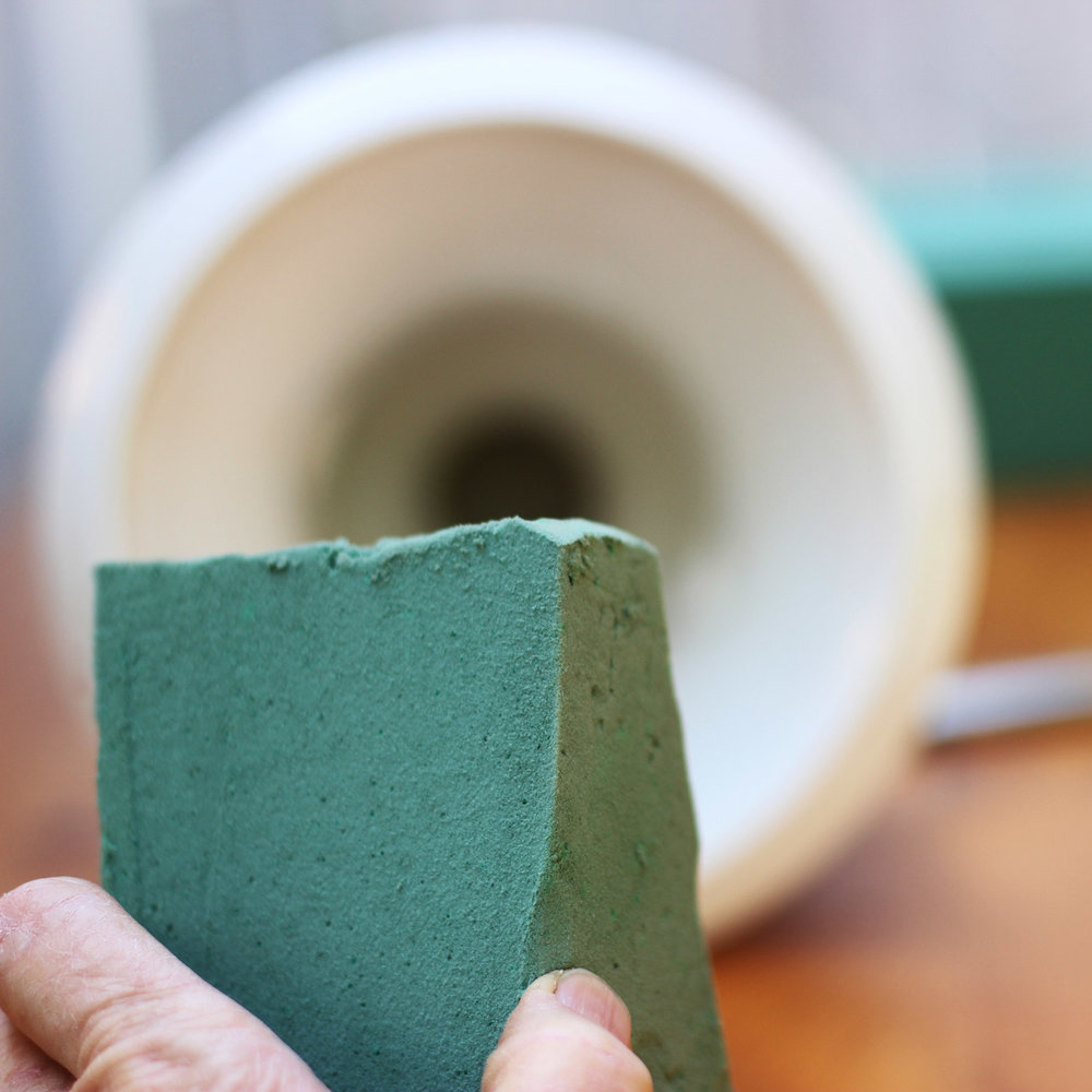 Cut part of a wet-pack brick to fit the bottom of the vase.
