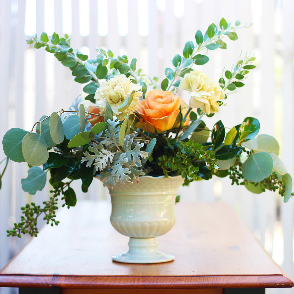 Add 3 orange Roses and 3 Dusty Miller.