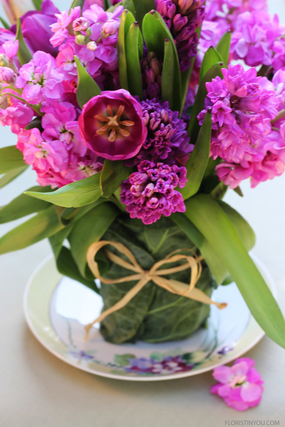 Arrangement sits on a vintage plate with a yellow rim &hand painted lavender flowers.