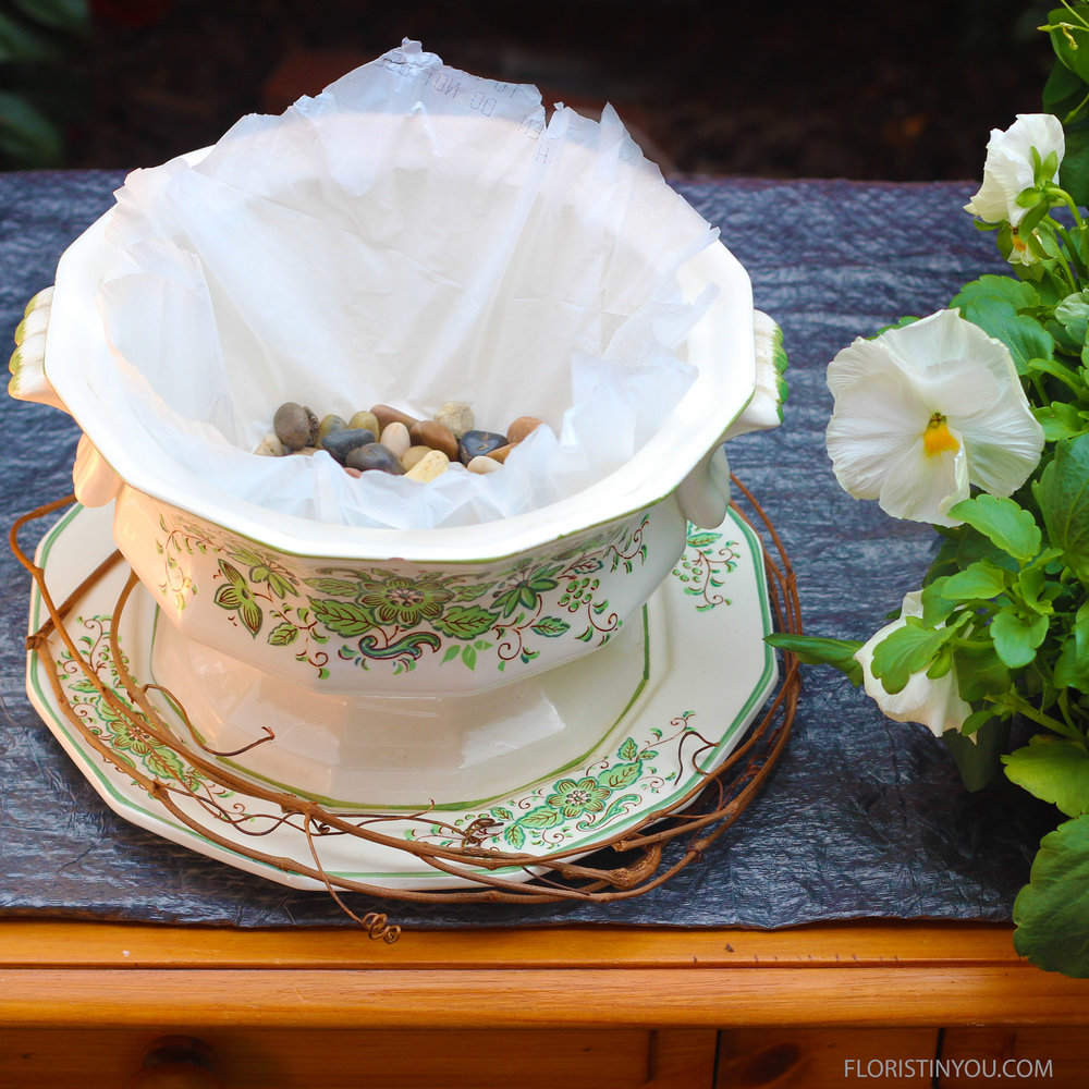 Put a trash liner in tureen.  Put a handful of pebbles or gravel in.
