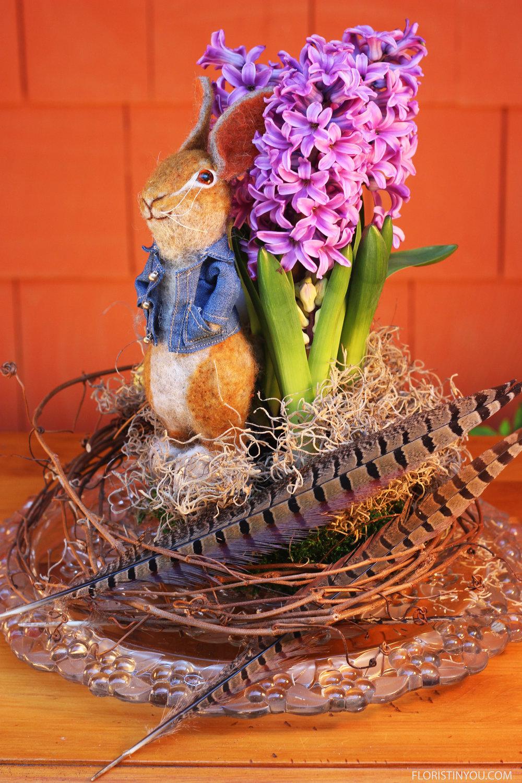 Put Spanish Moss around hyacinth. Put feathers on side.