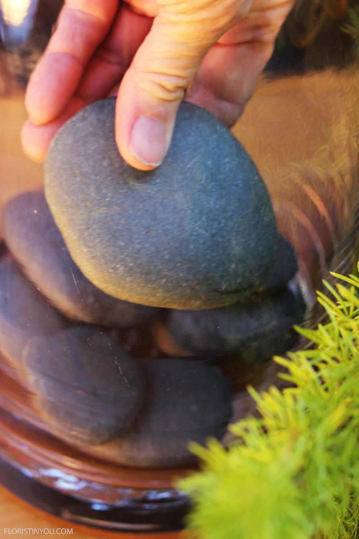 Carefully lay river rocks in bottom of vase.