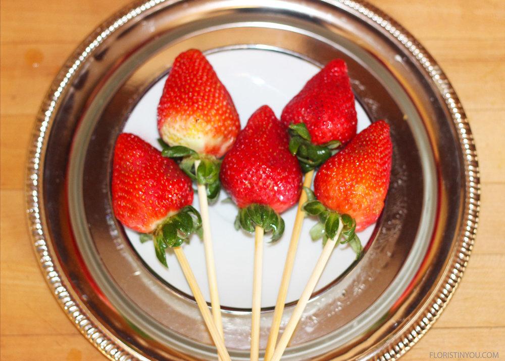 Put skewer into bottom of strawberries.