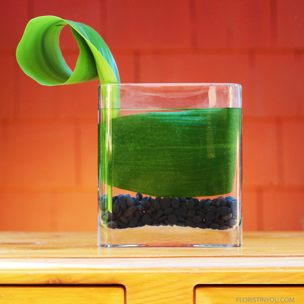 Slide leaf down inside of vase.