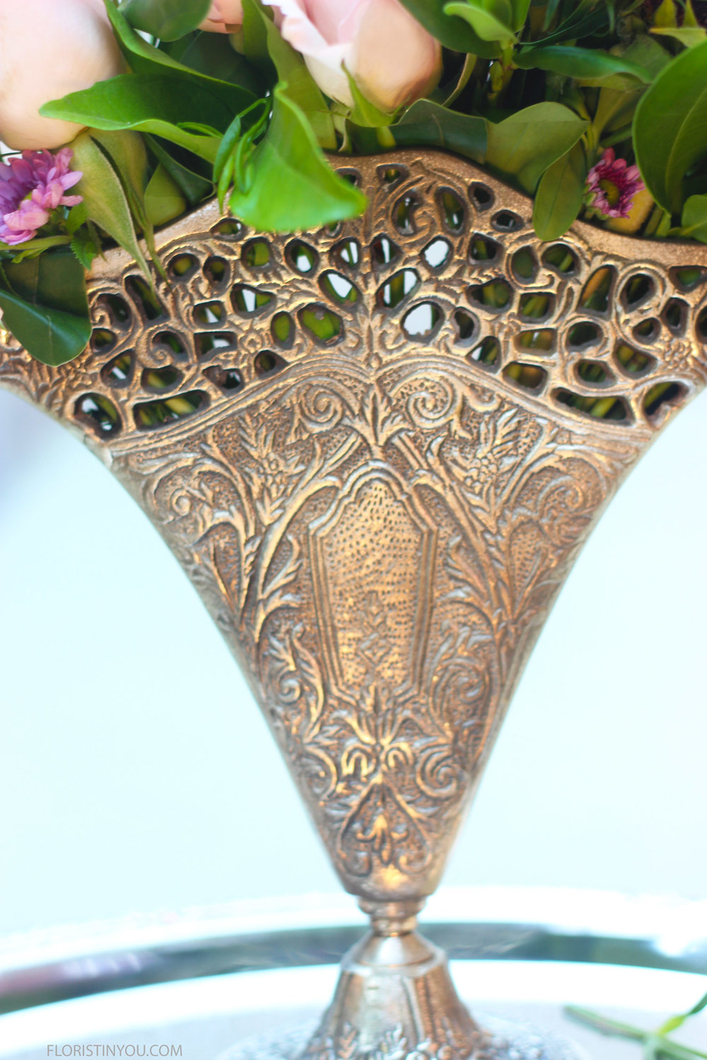 Note the intricate floral scroll work on the fan vase.
