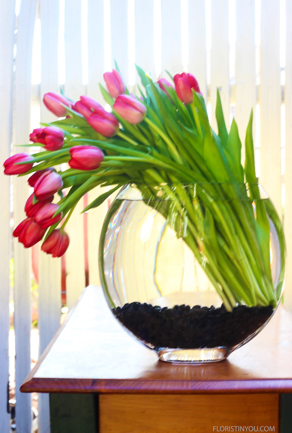Insert flowers. Keep stems together at bottom right. Lay flowers to rest on left side of vase.