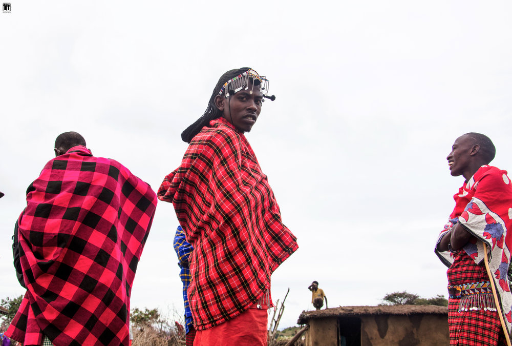 Some men hanging out in the center of the village while a women works on finishing the roof of a home. The Maasai homes are made 100% by the women.