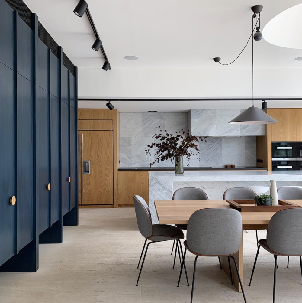 Dark blue stained veneered cabinetry - complimenting the timber veneers and the natural stone worktops