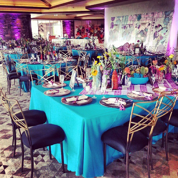 "The room glowed with teals & purples. Hand painted succulents in test tubes adorned the tables. A mural of the ""Royal Romantics"" series by LA artist Kelcey Fisher created an amazing backdrop for the reception."