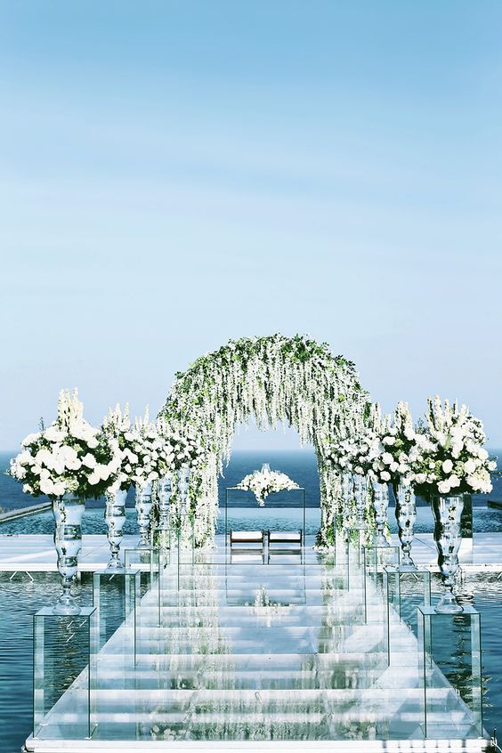 Floral arch to have a symmetrical design.Beach aisle features (2) tall lucite pedestals with floral arrangement.