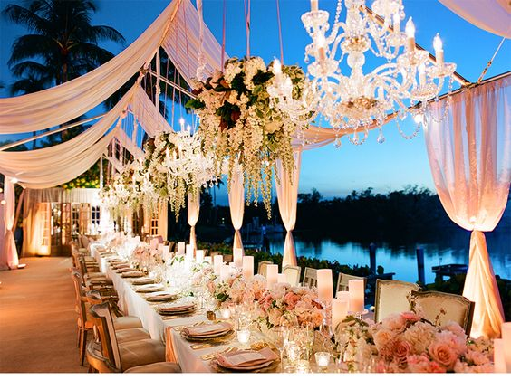 (2) Side family tables at 32' each with (8) small chandeliers and (9) florals hanging above. Arrangements similar to this mixed in with candles.