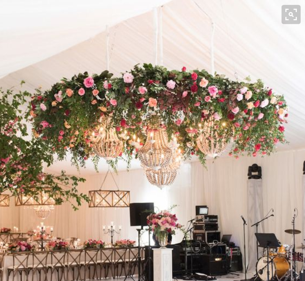 One large low floral chandelier with chandeliers underneath.