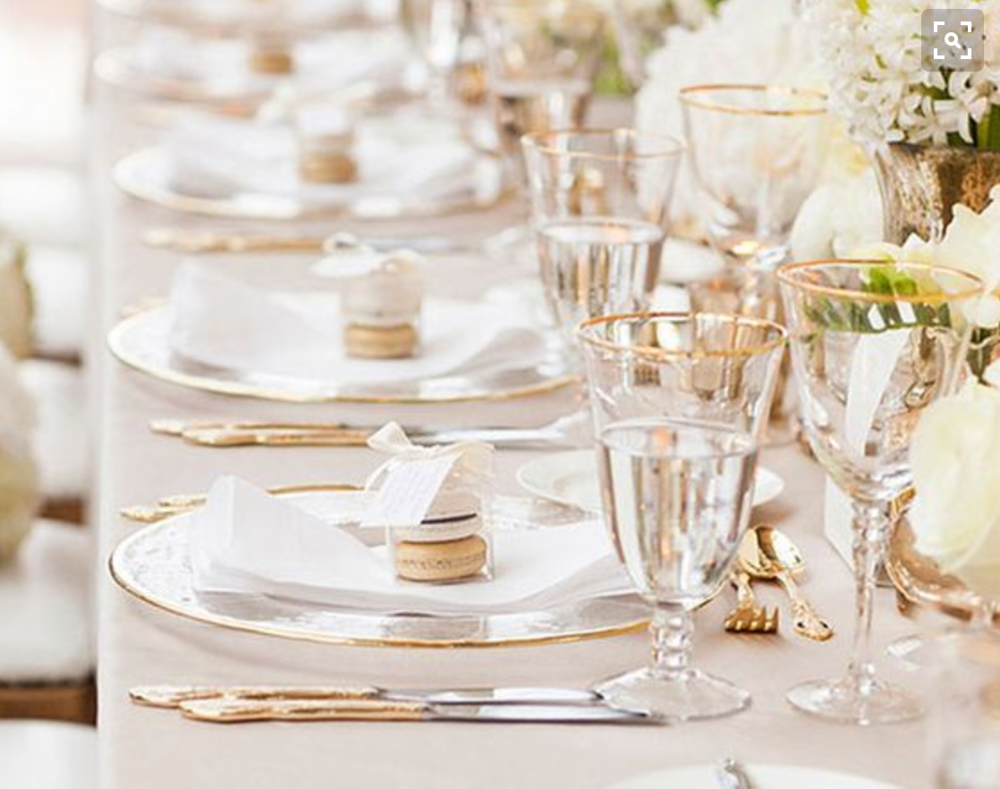 Gold rimmed glassware, clear china charger plate with gold rim, and golden flatware.