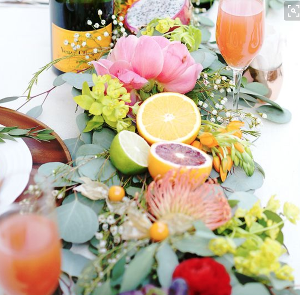 One Table with greenery runner and fruit.