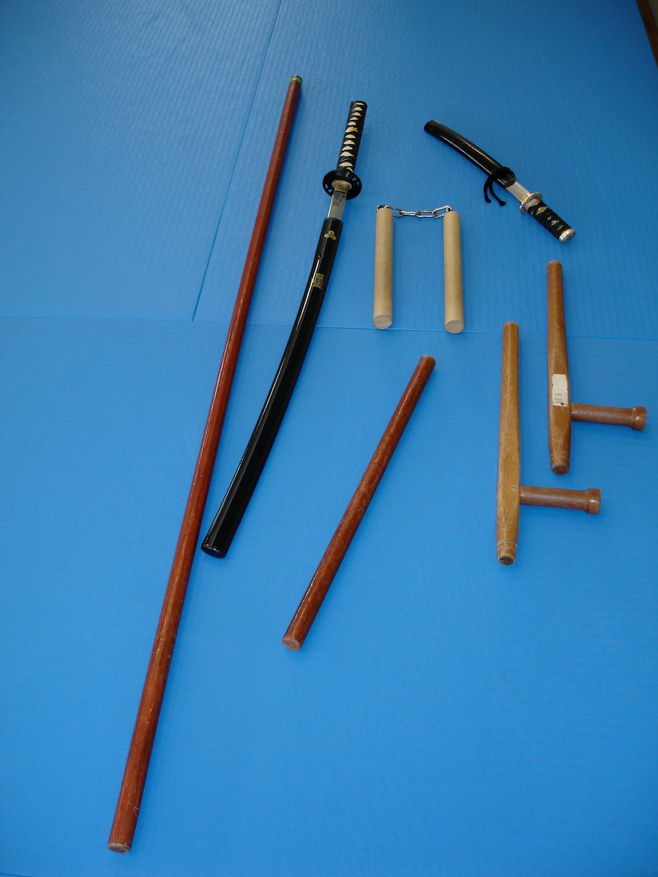 De gauche a droite, Baton (Bo) - Sabre (Katana) - Baton court (Tanbo) - Nunchaku - Couteau (Tanto) - Batons avec poignée (Tonfa)