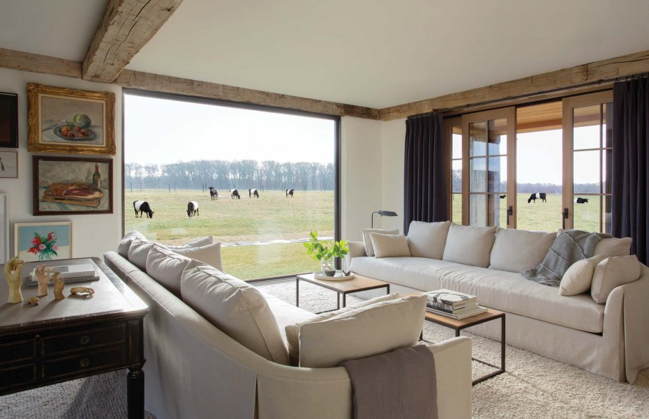 family room with views out to the grazing cows by  Hutker Architects