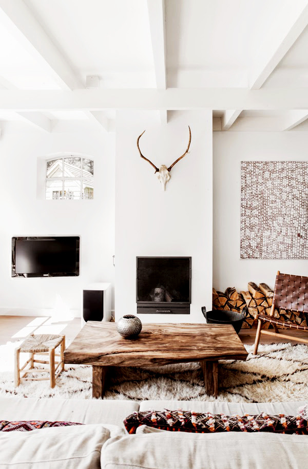 This living room shows key elements of Scandinavian design: neutral colors, white walls, warm woods, natural fibers and textures, and an open, airy feel.