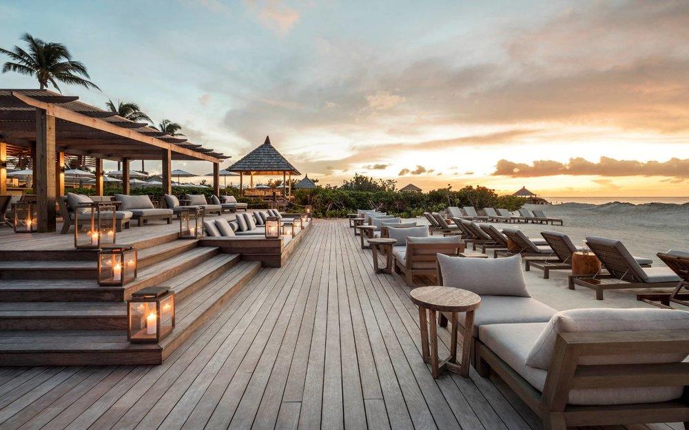 COMO-Parrot-Cay_COMO-Beach-Club_Deck--Sunset.jpg