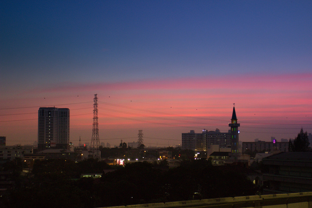 A mosque, powerlines and the evening skyline.