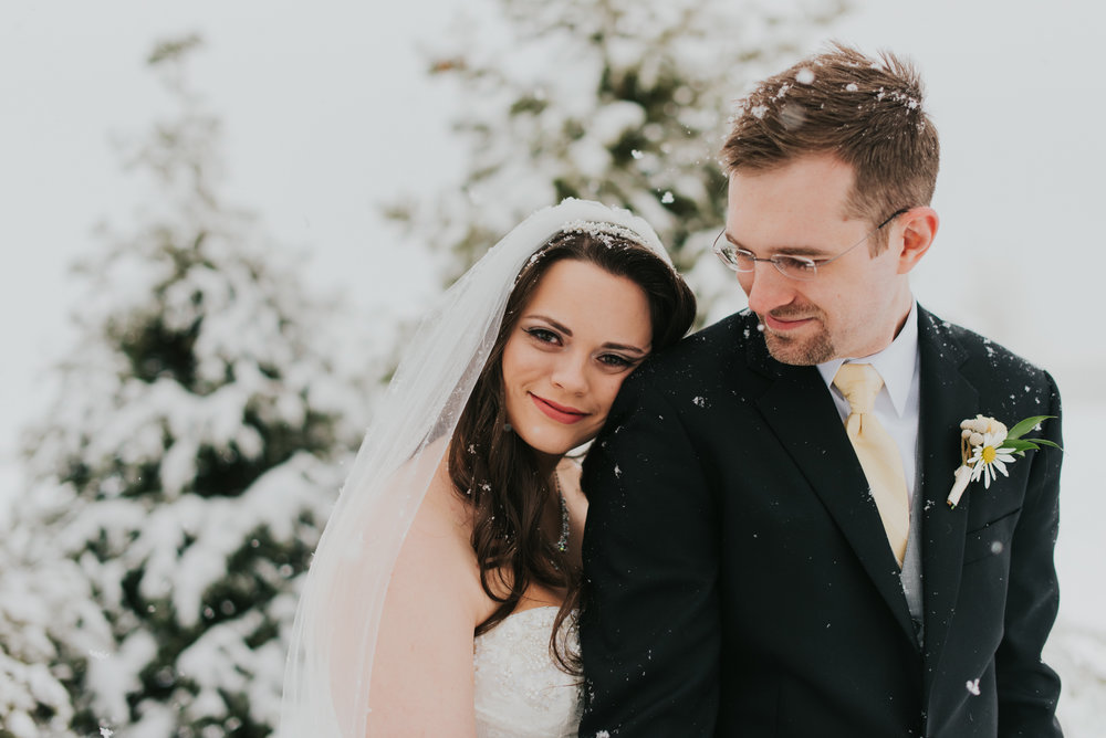 April and Jordan, snuggling in the snow outside of their wedding venue, the Windsor Estate Event Center in Windsor, Colorado.
