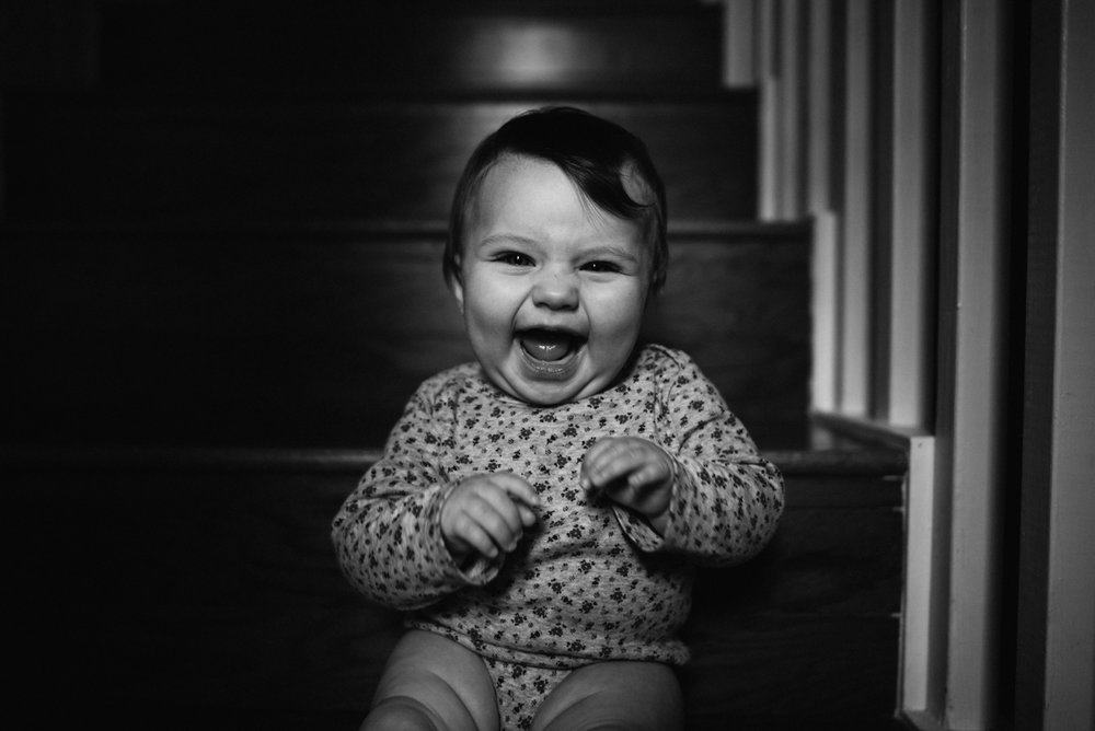 My daughter Luna, sitting at the bottom of our steps in our foyer. She sat on the edge and had the biggest smile on her face. She is the happiest baby I know, and I love taking her picture. Luckily, she is pretty easy to take photos of.
