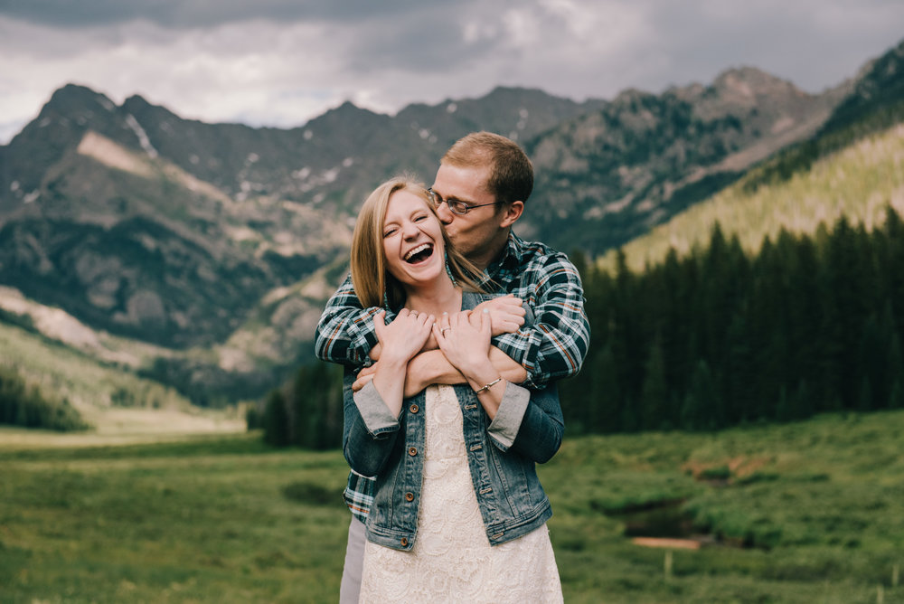 Erin is laughing as Clay gives her a huge hug during their Piney River Ranch engagement session in Vail, Colorado. They wanted to incorporate the Rocky Mountains, hiking, and their adorable Golden Retriever in their session. We hiked around Piney River, stopping in wildflower patches and by the lake, which they even went wading in!
