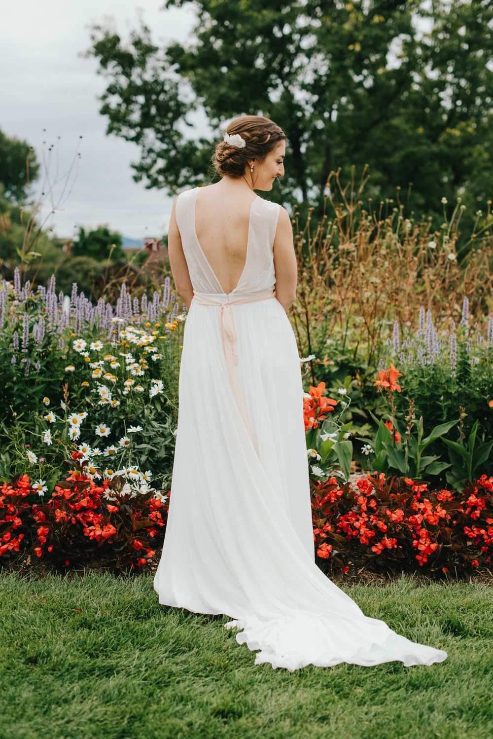 Lindsey standing in front of the beautiful wildflowers at Hudson Gardens on her wedding day. Her and Geoff decided that Hudson Gardens would be the perfect place for all of their friends and family to father for a wedding.