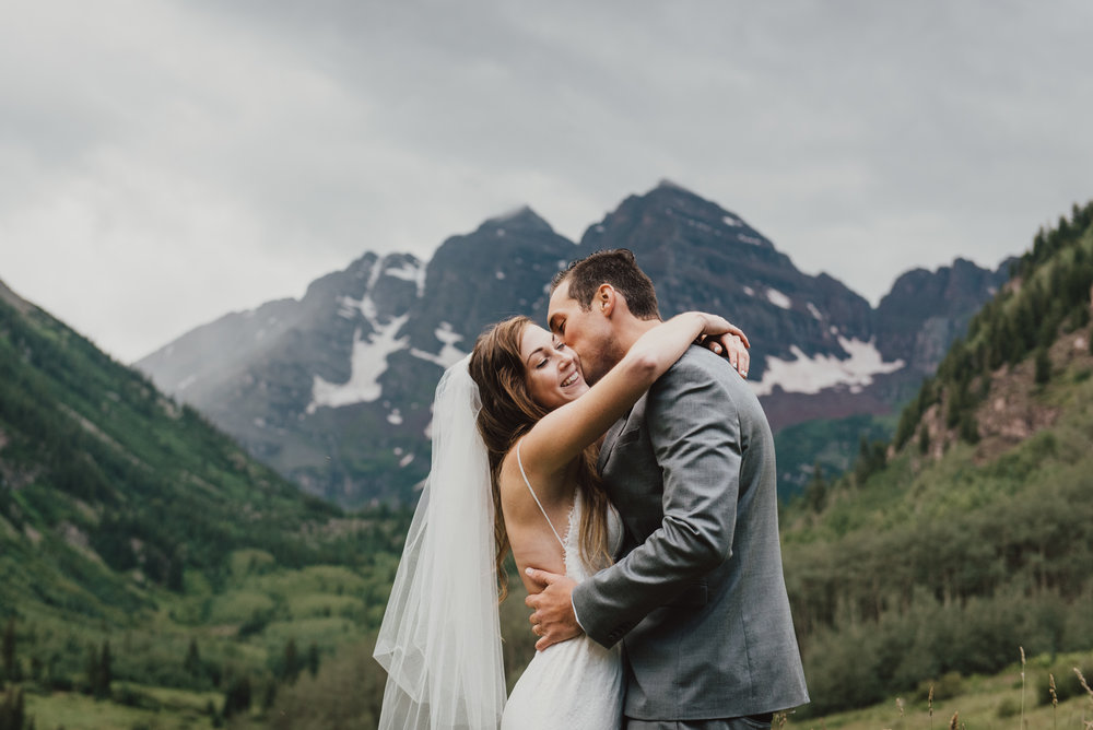 Heather and Darron in front of the Maroon Bells shortly after their destination elopement ceremony. It rained during the ceremony but it didn't matter, there was so much love and happiness, despite the rainy mountain wedding! Here the rain stopped for a little bit to get us some awesome Maroon Bells bridal portraits!