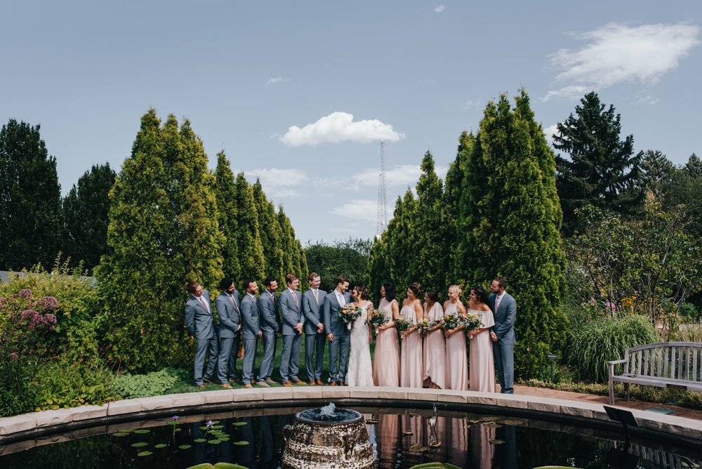 Nicole and Jamie with their bridal party at their Denver Botanic Gardens wedding. Here is a shot of the wedding party, wearing blush and grey, in front of one of the ponds at the gardens.
