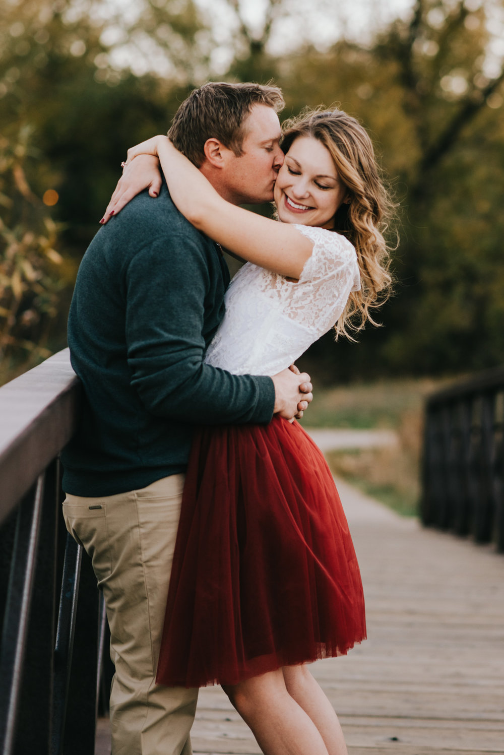 A couple embracing on a bridge at their Denver engagement session.