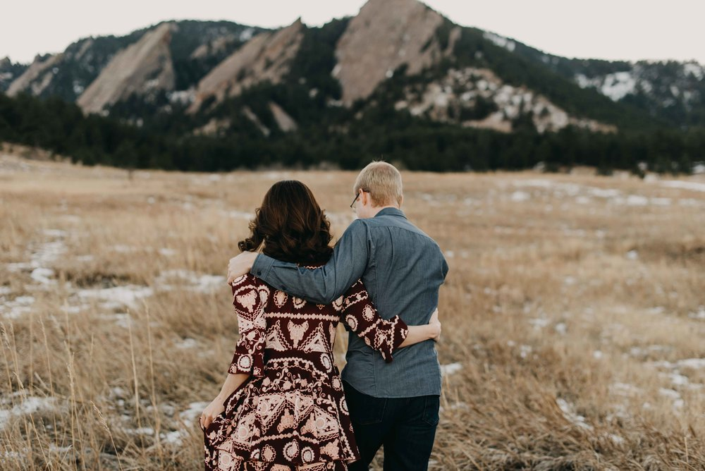 Trinity and Peter walking towards the flatirons during their Chautauqua engagement adventure session. It was super cold to a lot of embracing was a must!