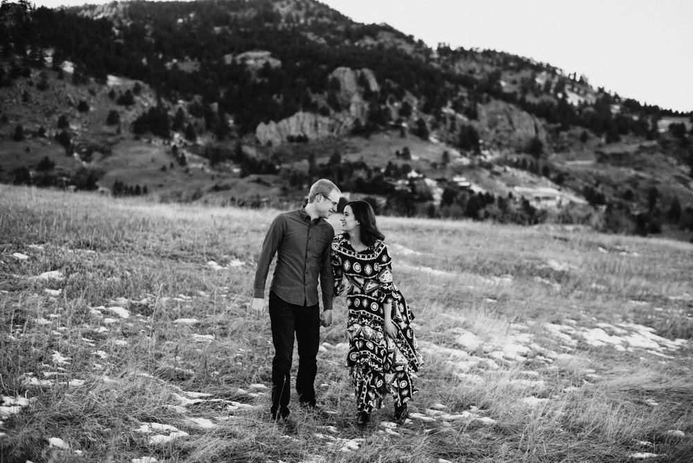 Trinity and Peter walking hand in hand during their Boulder Engagement Session in Chautauqua.