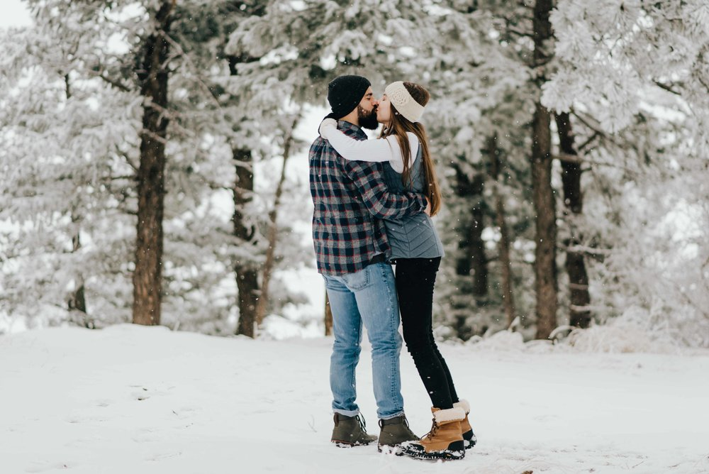 Nik and Tani kissing during their snowy engagement session in Golden, Colorado!