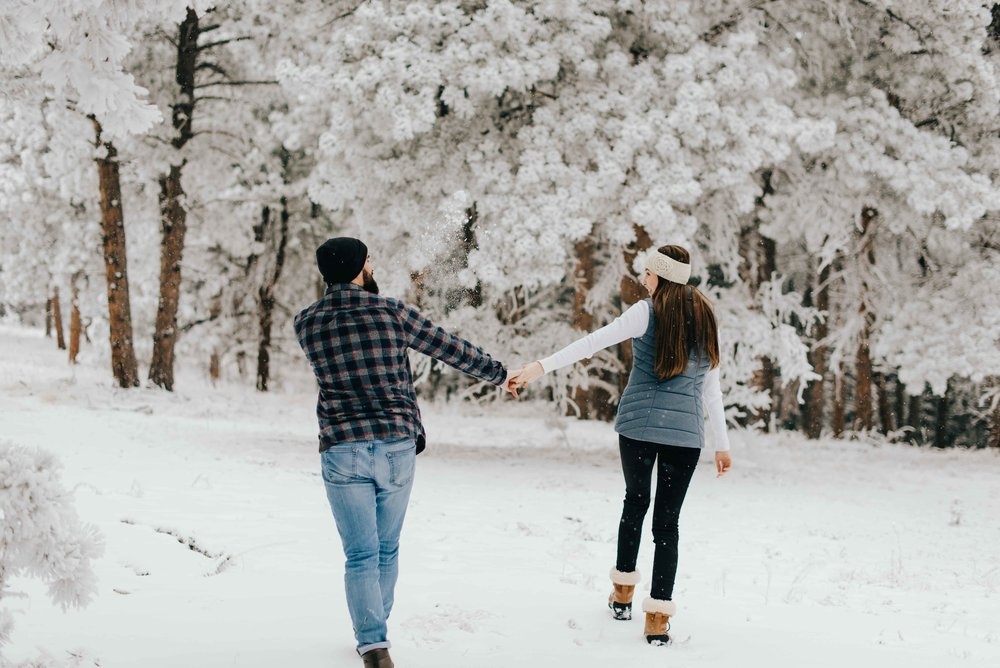 Nik and Tani walking hand in hand and playing with snow during their adventure couples session on a snowy day in Colorado.
