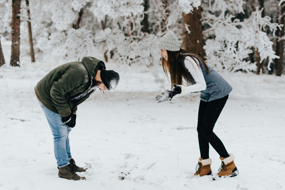 Tani feeling pride and perhaps some remorse at throwing a snowball at Niks face. They had an amazing snowball fight during their rocky mountain adventure engagement session!