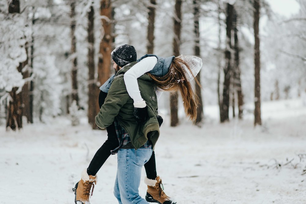 Nik keeping Tani from throwing more snowballs at his face during their snowy mountain engagement session.